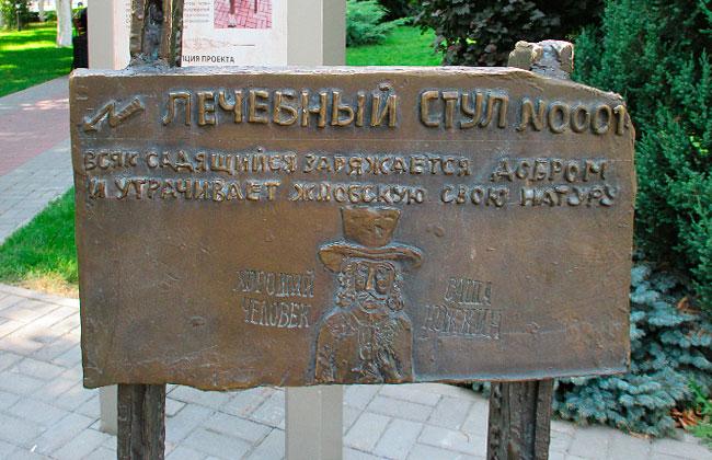 Надпись на спинке памятника Лечебный стул в Воронеже